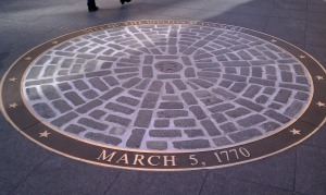 1886, the place where Crispus Attucks and Samuel Gray fell were marked by circles on the pavement. Within each circle, a hub with spokes leads out to form a wheel.
