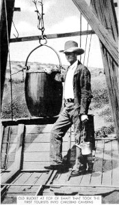 Jim White standing next to a guano bucket atop the guano shaft at Carlsbad Caverns. The bucket was used to carry the first tourists into the caverns. He is holding one of his homemade kerosene lanterns.