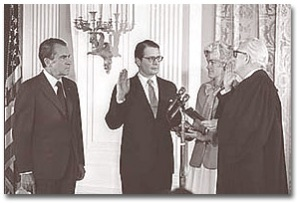 Elliot Richardson is sworn in as Secretary of Defense in February of 1973. President Nixon looks on as Richardson's wife, Anne, holds the Bible and Chief Justice Warren Burger swears him in at the White House.