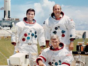 The prime crew for the Apollo 17 lunar landing mission are: Commander, Eugene A. Cernan (seated), Command Module pilot Ronald E. Evans (standing on right), and Lunar Module pilot, Harrison H. Schmitt. They are photographed with a Lunar Roving Vehicle (LRV) trainer. Cernan and Schmitt will use an LRV during their exploration of the Taurus-Littrow landing site. The Apollo 17 Saturn V Moon rocket is in the background. This picture was taken at Pad A, Launch Complex 39, Kennedy Space Center (KSC), Florida.