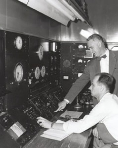 Walter Zinn (standing) presses a button to shut down the Chicago Pile-3 research reactor