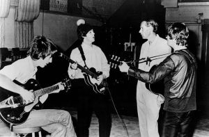Publicity photo of the Beatles with producer George Martin in the studio at Abbey Road.